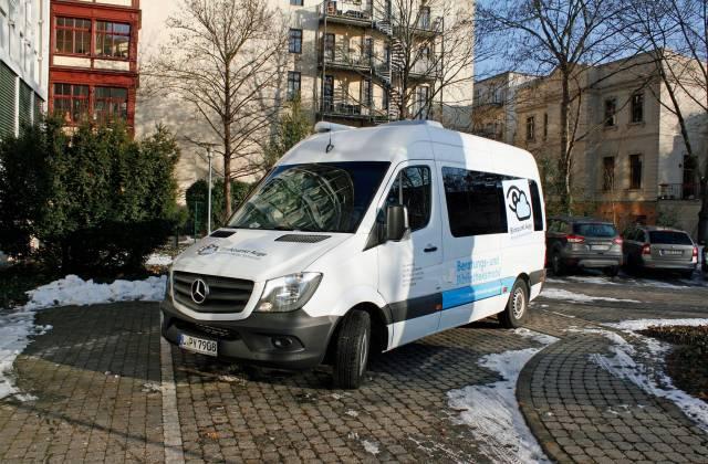 weißer bedruckter Kleinbus auf der Parkfläche vor der DZB.