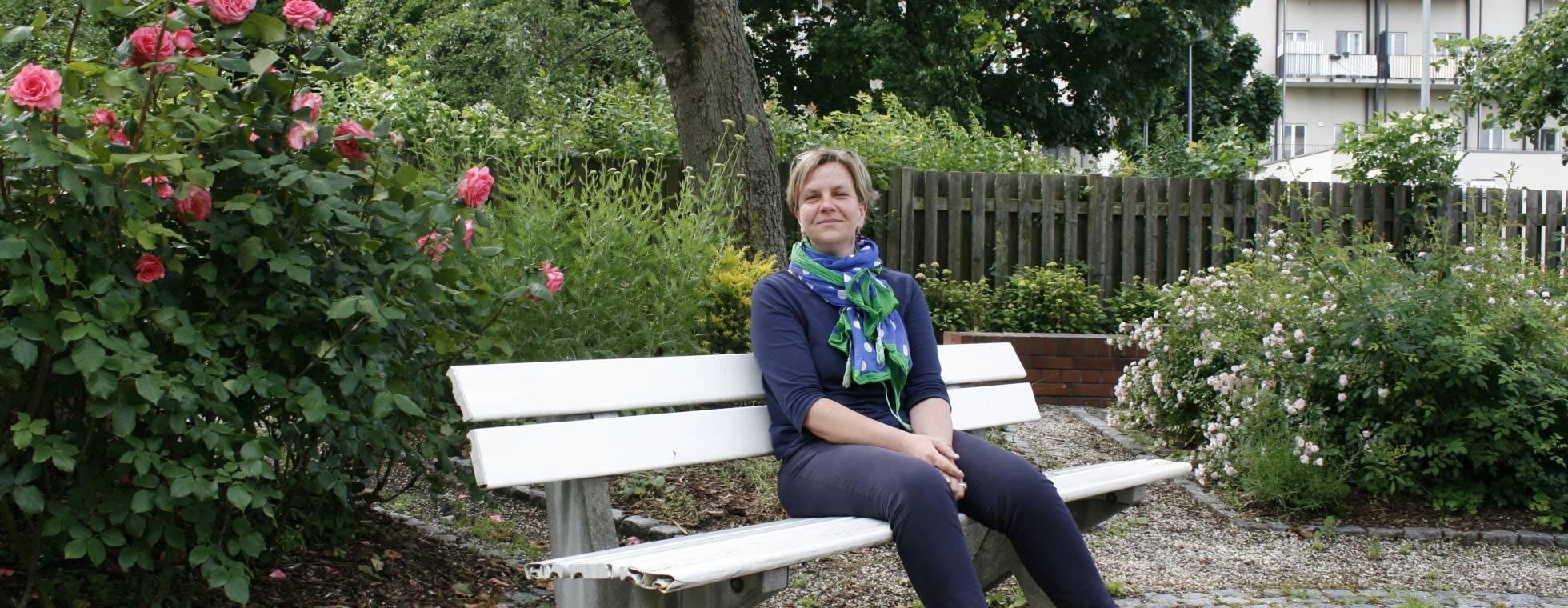 Eine Frau sitzt auf einer Parkbank im Innenhof der DZB