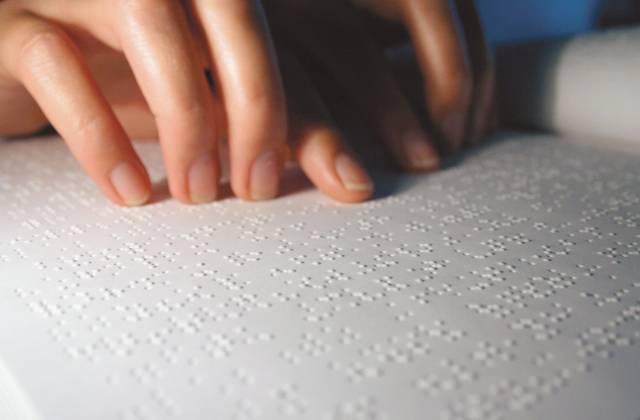 Finder die über ein Braillebuch streichen