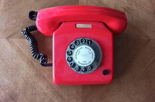Rotes altes Telefon auf einem Tisch stehend
